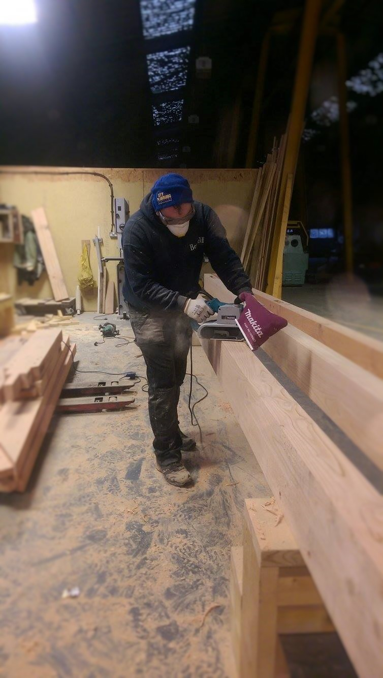 Sanding down the rough-sawn timber to bring out the natural beauty, at the workshops of Benfield ATT