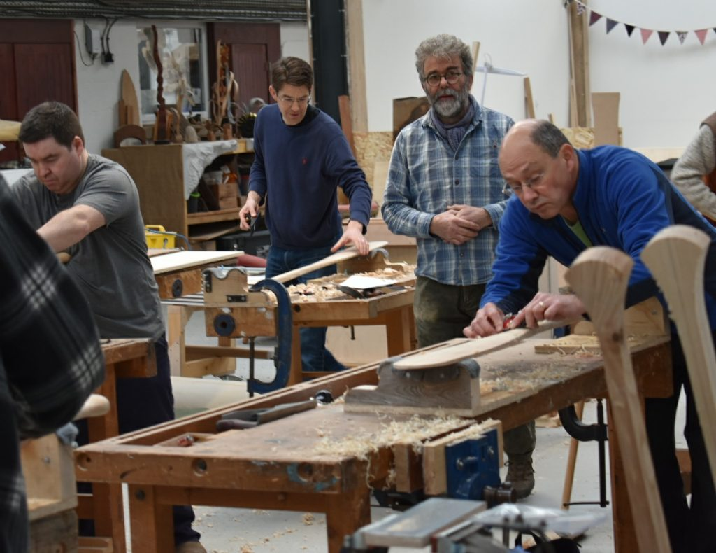 Colin Henwood with students making a canoe paddle at the Sylva Wood Centre