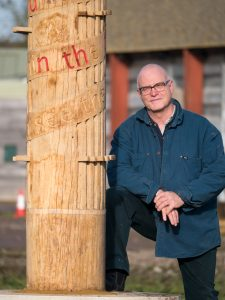 Sculptor Simon Clements standing next to the Charter Pole at the Sylva Wood Centre